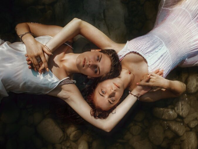 calm female couple lying in water