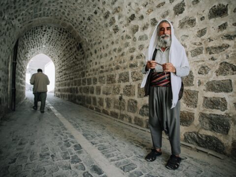 ethnic bearded man with prayer beads near rough temple wall