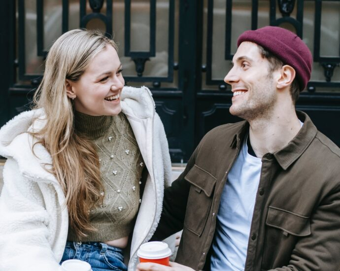 happy young man and woman drinking coffee near big building