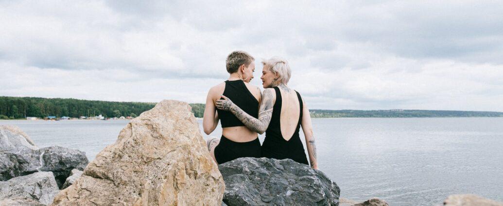 photo of women sitting on rocks near sea